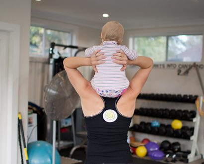 strong fit healthy mum with baby on shoulders in gym