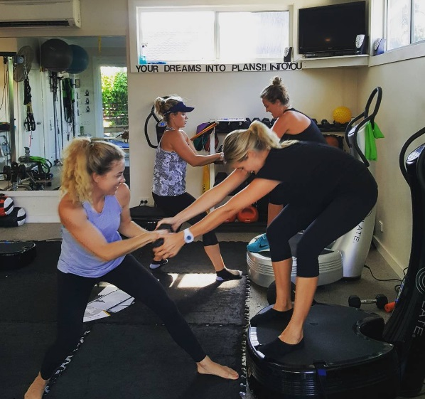 four women training with power plate anddumbells