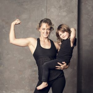 Strong Clare Hozack with daughter on hip modelling strength