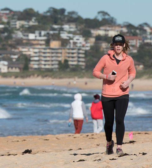 fit strong healthy mother running runs run on beach