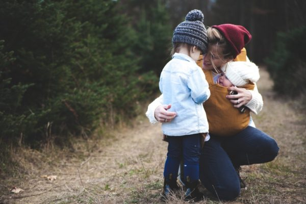 mother crouching on forest trail with baby in carrier and toddler