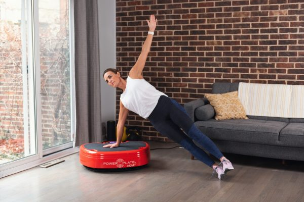 Woman performing a side plank balance yoga exercise on Power Plate whole body vibration
