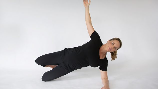 pregnant woman performing a side hover plank oblique training