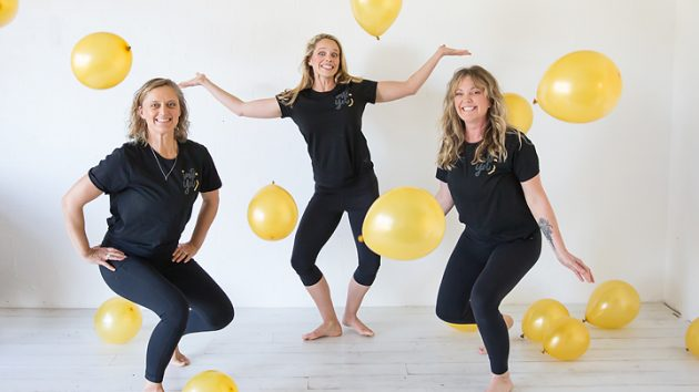 three women crouching with balloons and big smiles