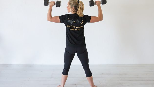 strong woman holding weights intoyou IntoYou heavy lifting