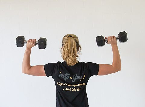 Image of strong woman holding weights