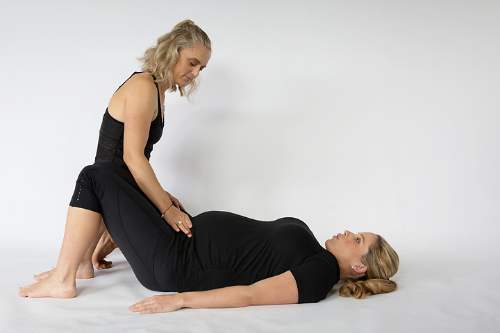 personal trainer training a woman through pregnancy with deep core testing