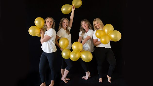 Four women playing with balloons team building bonding