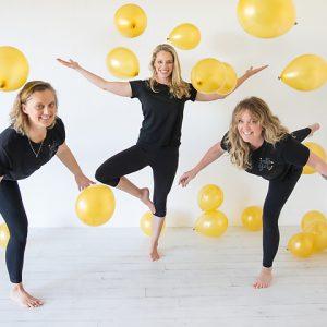 three women balancing on one leg with ballloons
